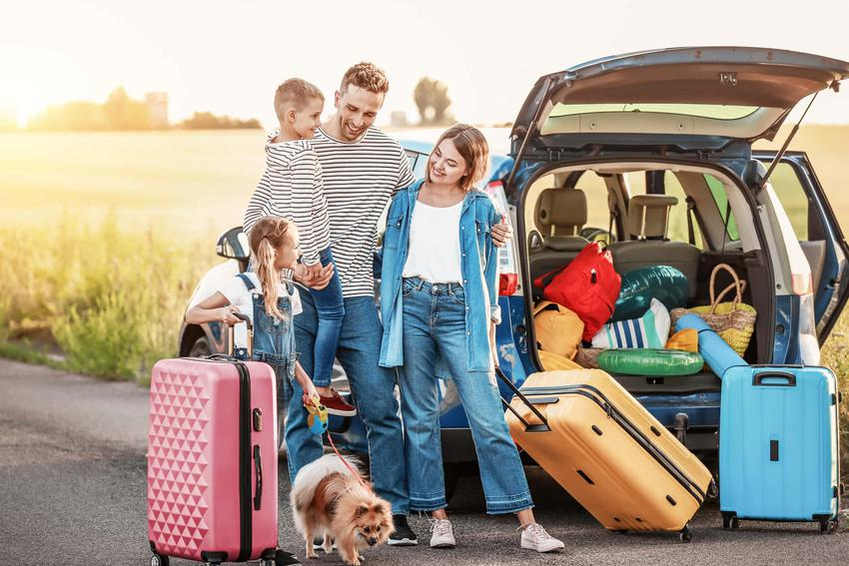 Rodzina z dziećmi i psem stoją przy samochodzie wypełnionym podróżnymi torbami, psiarze na wakacjach, czyli gdzie podróżować z czworonogiem