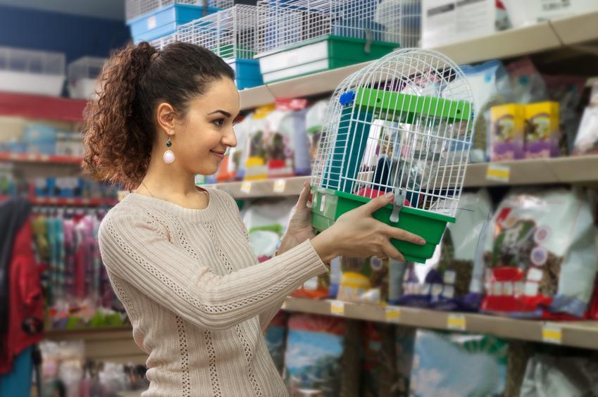 Kobieta oglądająca klatkę dla chomika w sklepie, a także klatka dla chomika i jej rodzaje