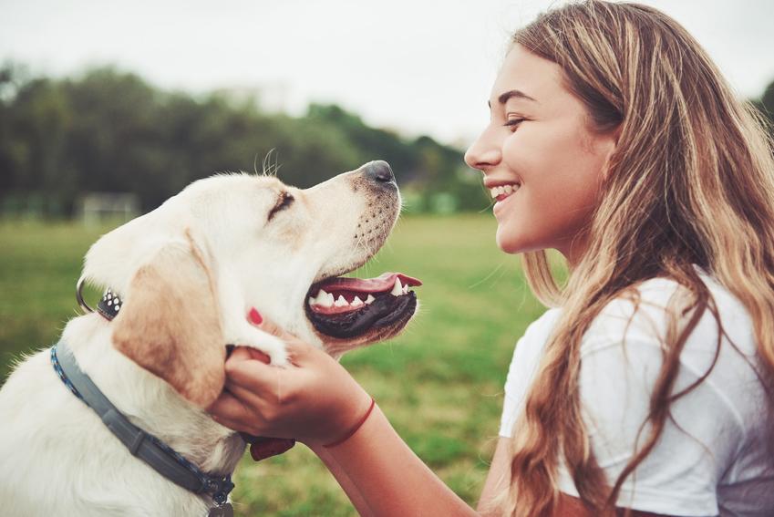 Kobieta uśmiechająca się do psa, a także najlepsze imiona dla psa samca